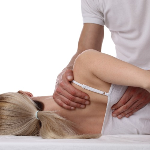 Back view of a woman on her side receiving an osteopathic treatment